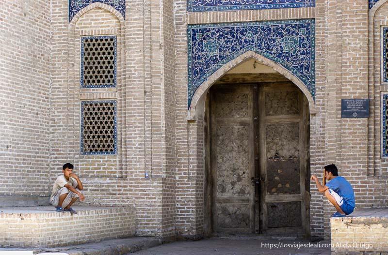 jóvenes sentados en cuclillas junto a madrasa de bukhara
