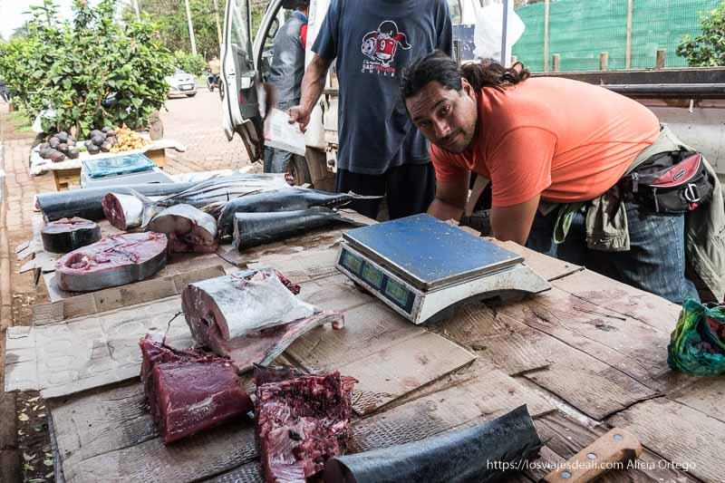 puesto de pescado en la calle con rapa nui mirando a la cámara cómo es viajar a Isla de Pascua