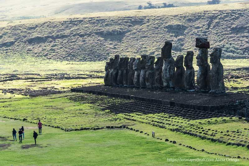 fila de 15 moais con plataforma de piedra alrededor y visitantes pequeñitos a su lado cómo es viajar a Isla de Pascua