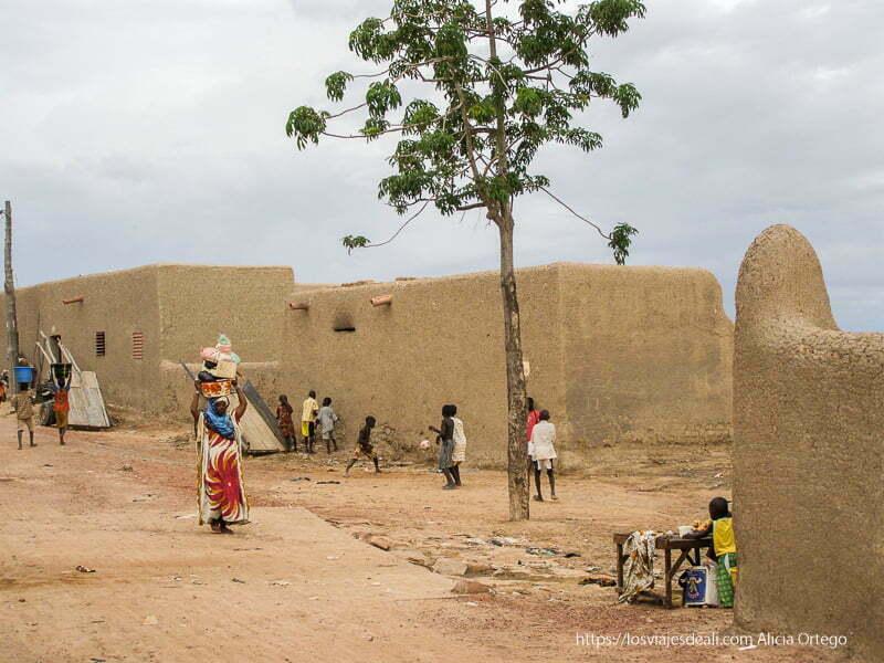 edificios de adobe y una mujer llevando muchas cosas en la cabeza djenne en su dia de mercado