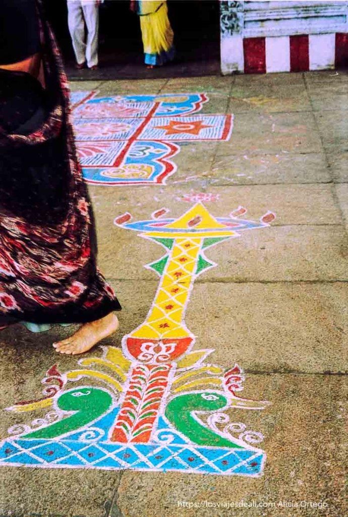 suelo pintado con figuras de colores y una mujer pasando con su sari tamil nadu