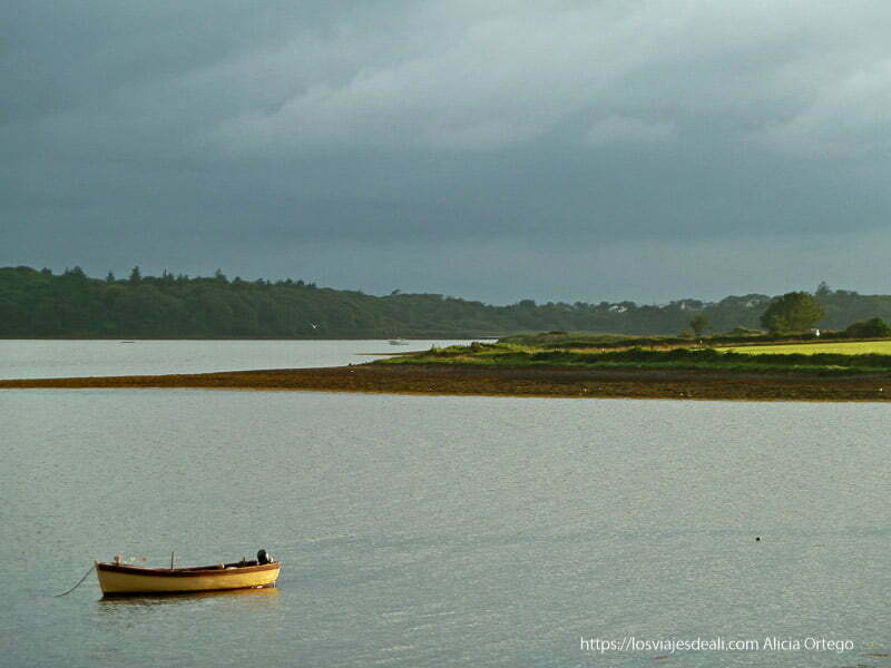 bahía de dingle al atardecer con barca iluminada por sol