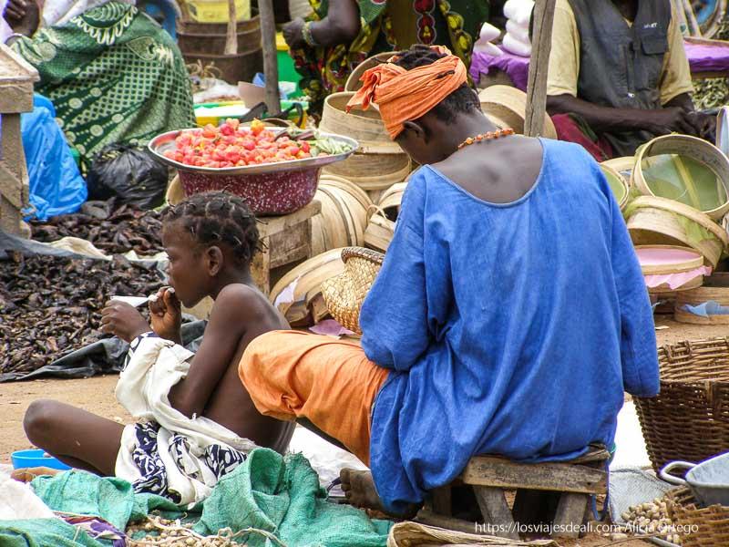 vendedora y su hija entre puestos del mercado y color djenne en su dia de mercado