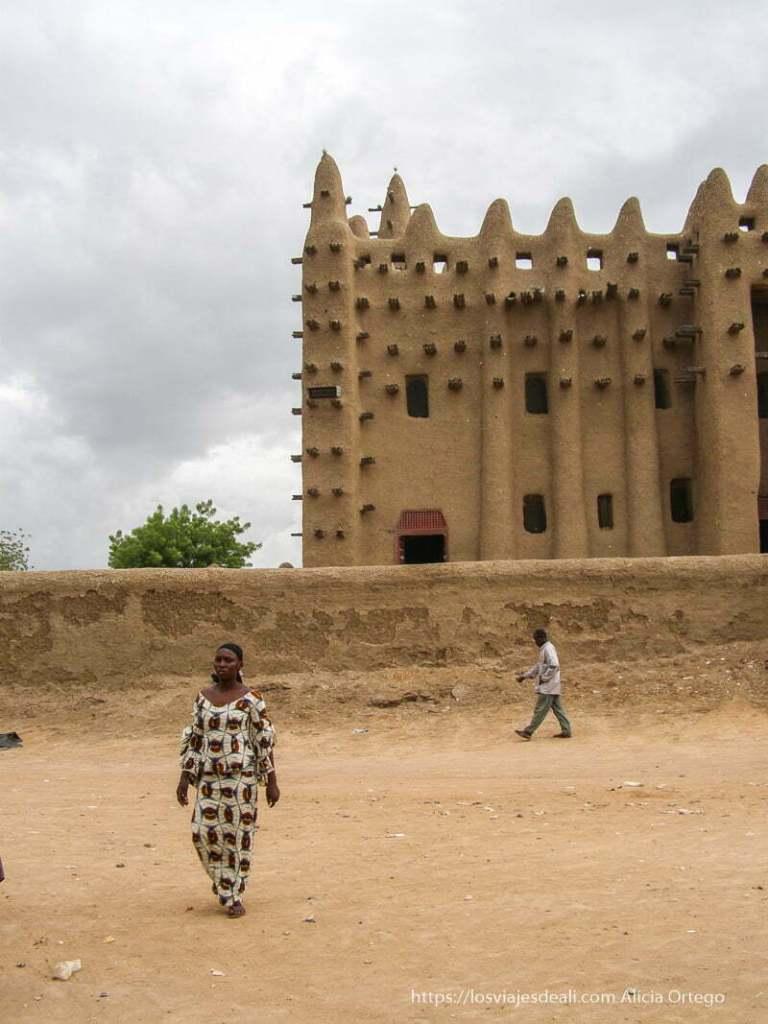 mezquita con mujer vestida de colores andando delante djenne en su dia de mercado