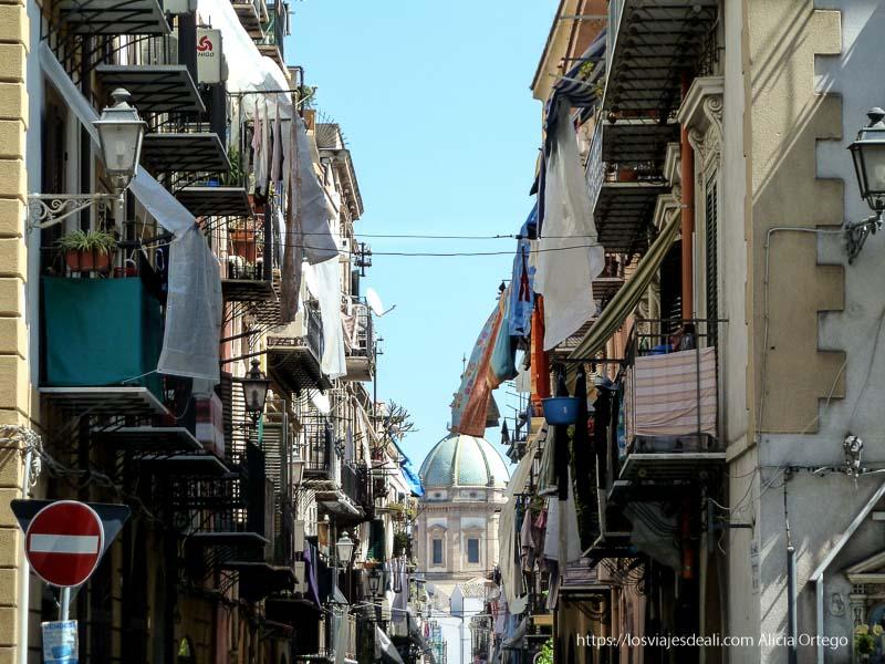 cúpula de iglesia al fondo de calle llena de balcones con ropa tendida