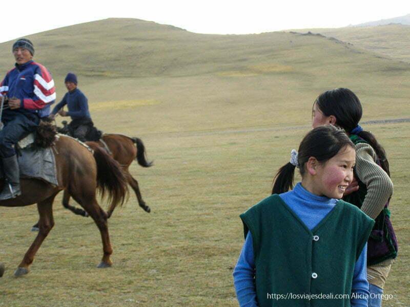 niñas kirguises mirando a los jinetes