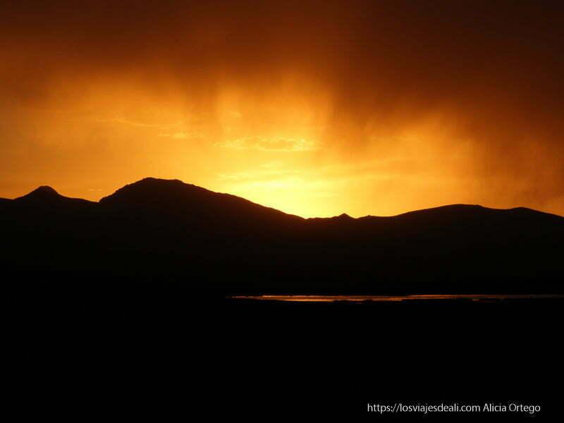 atardecer que parece un incendio tras las montañas en el lago song kol