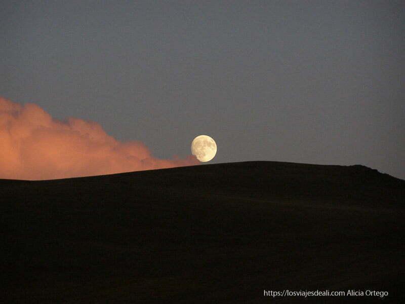 luna llena encima de una monte y con nube teñida de rojo al lado en el lago song kol
