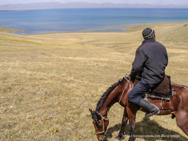 kirguis en su caballo mirando al lago song kol desde lo alto de una loma