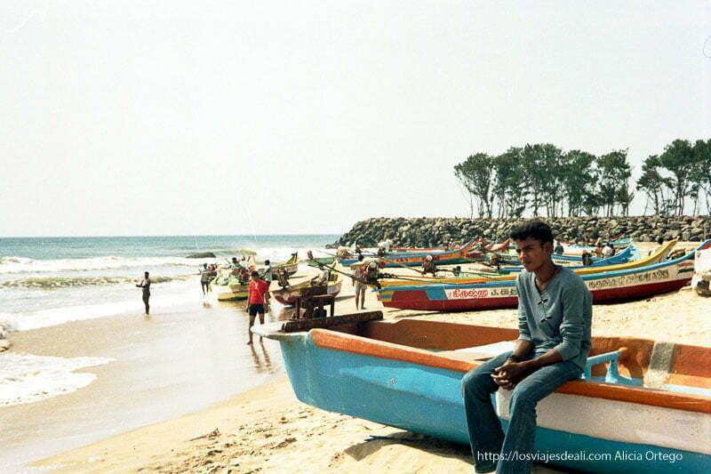 joven de mamallapuram sentado en una barca en playa tamil nadu