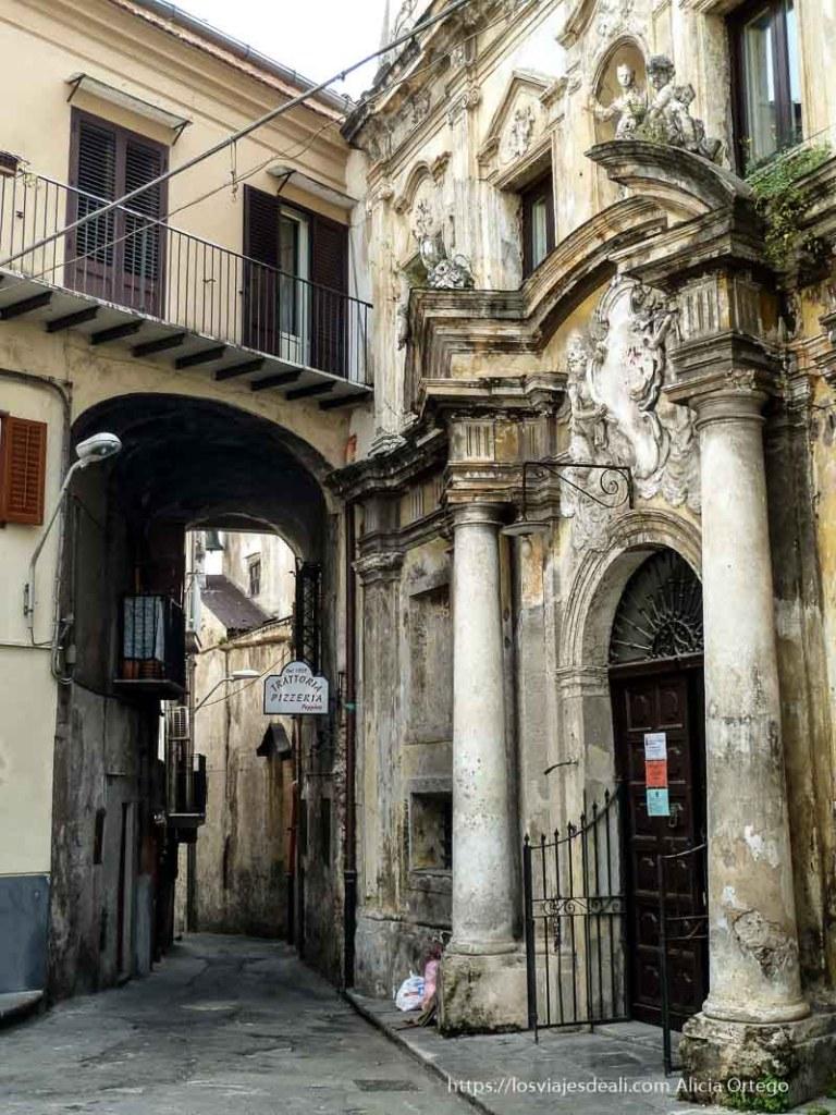 calle de monreale con gran portal barroco que se cae de viejo