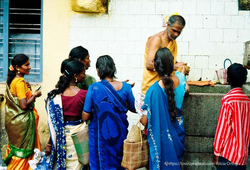hombre dando pan a mujeres con saris en templo de mysore