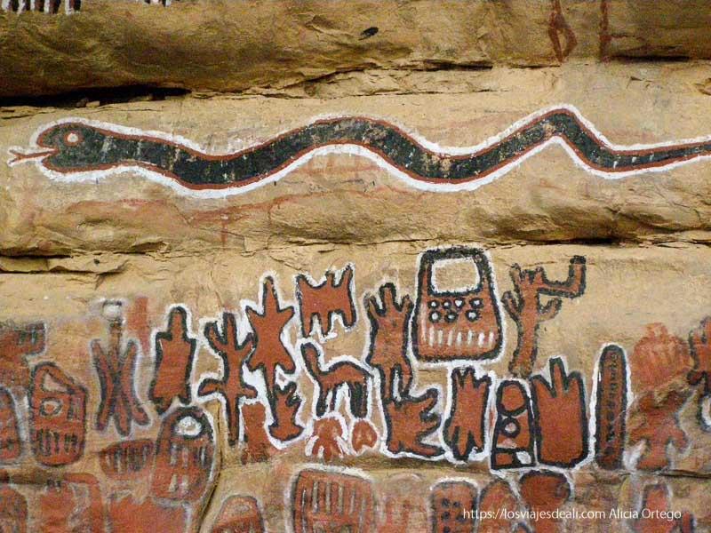 figuras pintadas de rojo, blanco y negro con una gran serpiente en la parte superior pais dogon