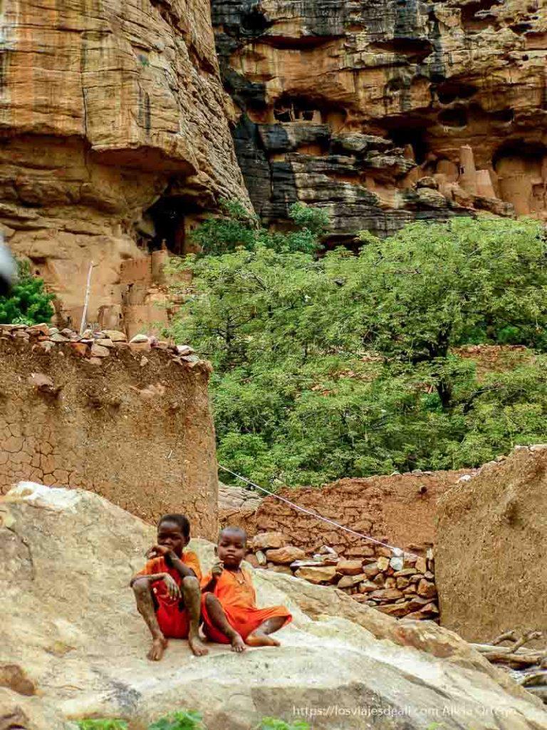 dos niños vestidos de naranja nos observan desde una roca pais dogon