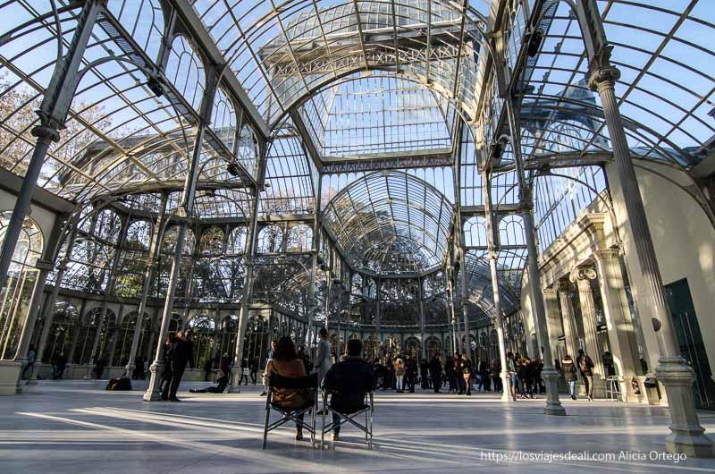 pareja sentada en sillas en el centro del palacio de cristal de el retiro