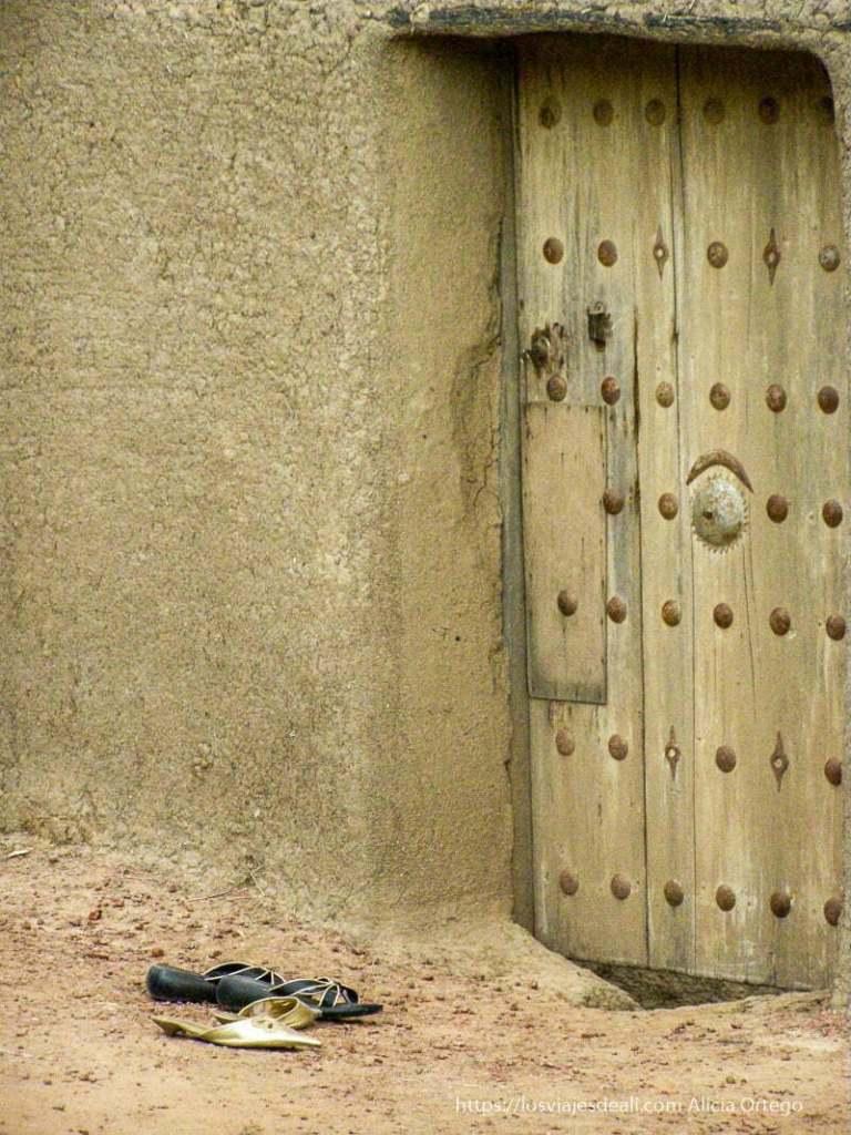 puerta con remaches metálicos y sandalias en la calle djenne en su dia de mercado