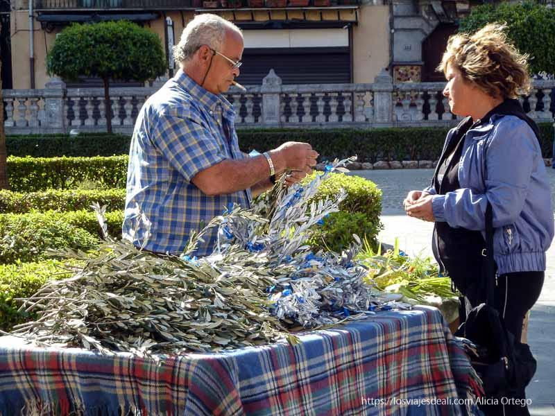 puesto de venta de ramas de olivo y señora comprando
