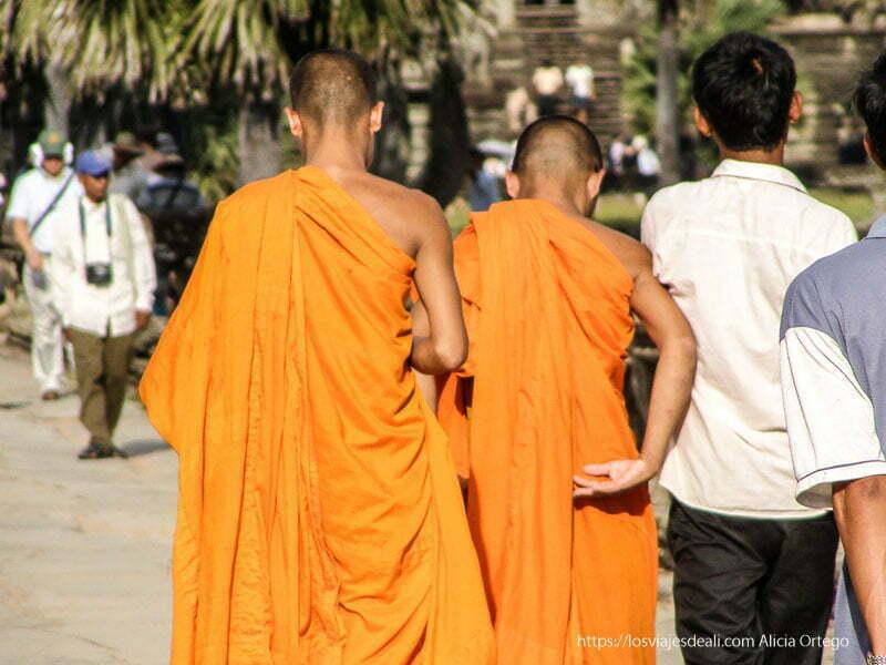 dos monjes con túnicas naranjas en templos de angkor