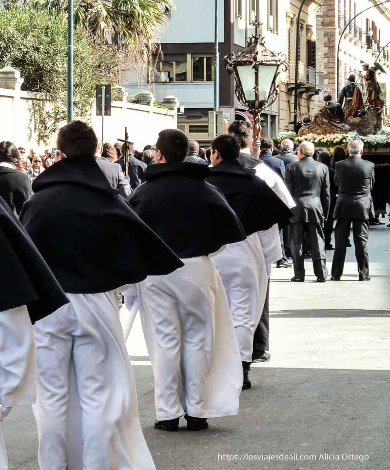 novicios con sotana blanca y capelina negra detrás de un paso Trapani en semana santa