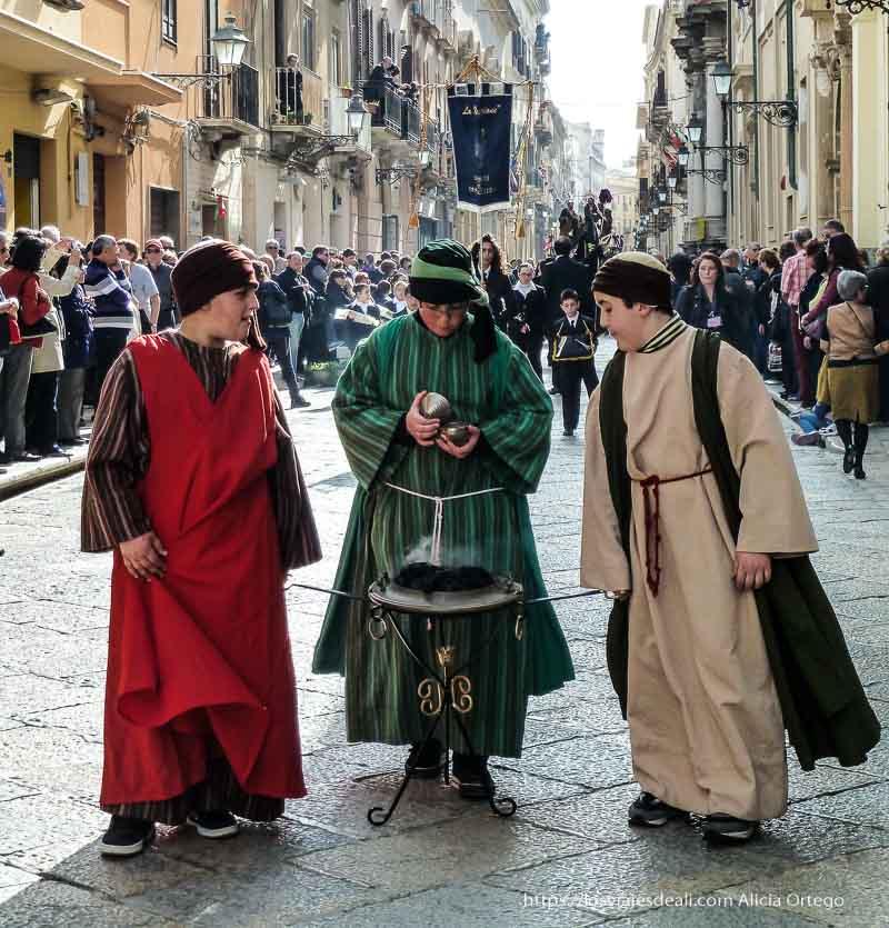 tres niños en la procesión llevando pebetero de incienso y disfrazados de medievo Trapani en semana santa