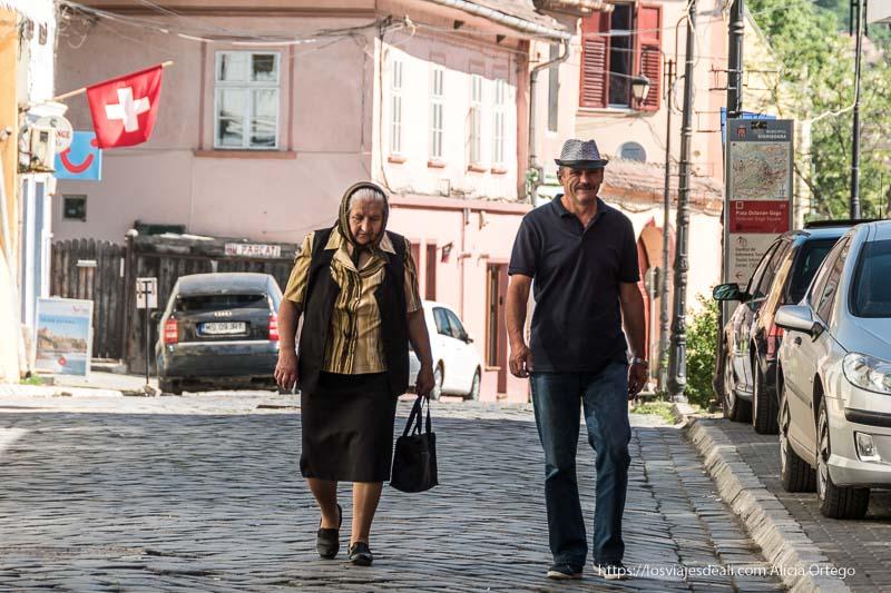 señora con pañuelo en la cabeza y señor con gorro andando por sighisoara