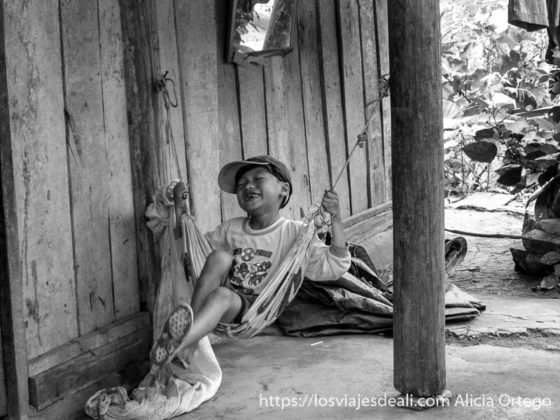 niño balanceándose en una hamaca y riéndose en el norte de vietnam