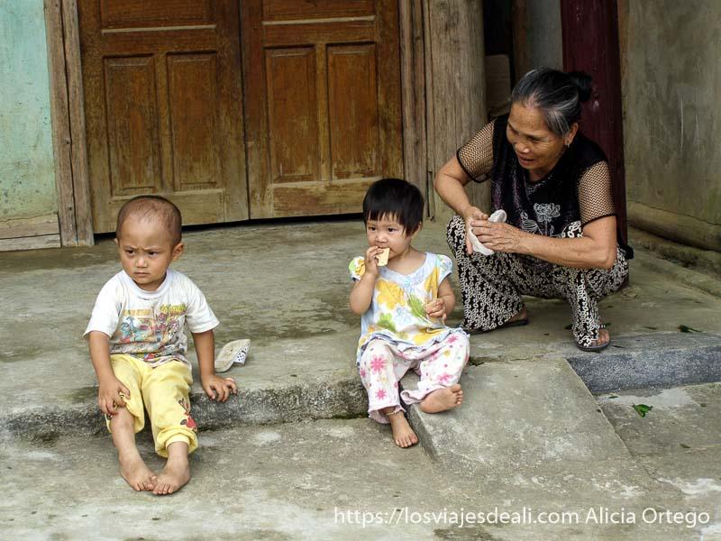 abuela con sus dos nietos sentados en la puerta de casa el norte de vietnam