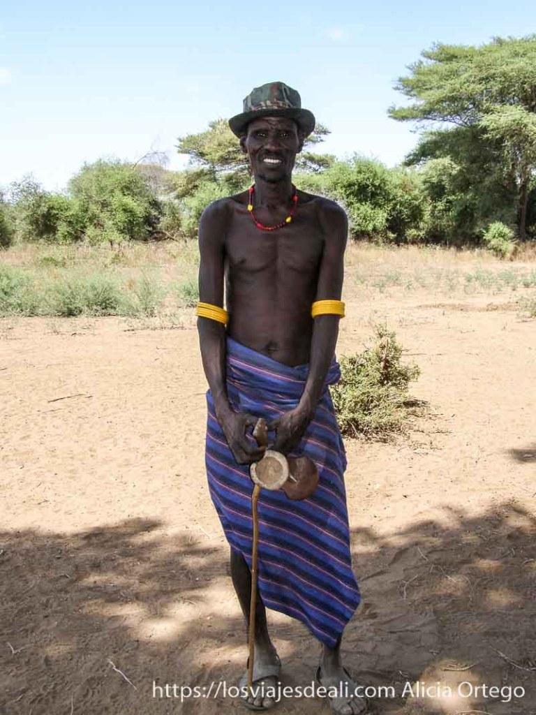 hombre de la tribu dasanech con tela de rallas a modo de falda, su bastón y banqueta pequeña