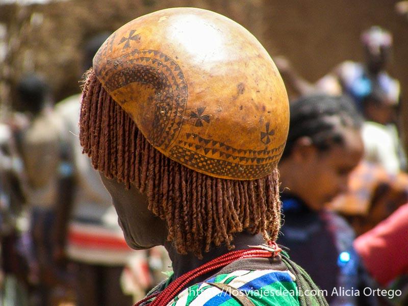 mujer con pelo de trencitas y calabaza con dibujos como sombrero mercados del sur etíope