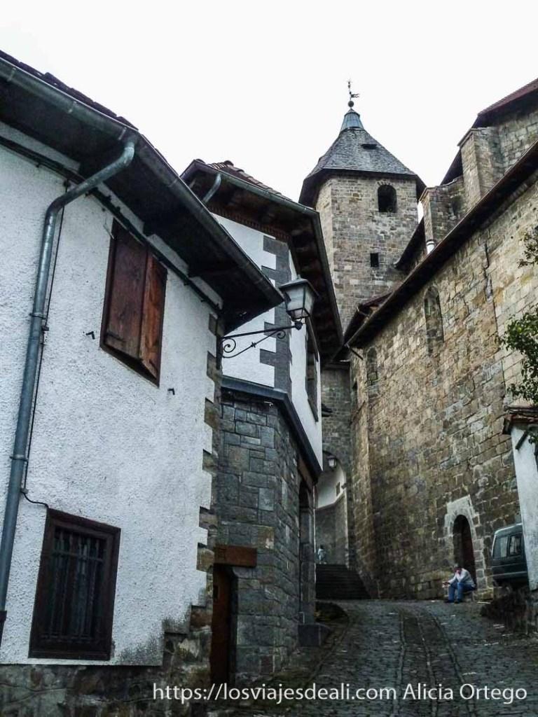 calle con casas de piedra y torre de iglesia al fondo