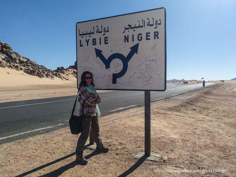 posando junto a cartel de carretera que señala dirección a Níger y Libia