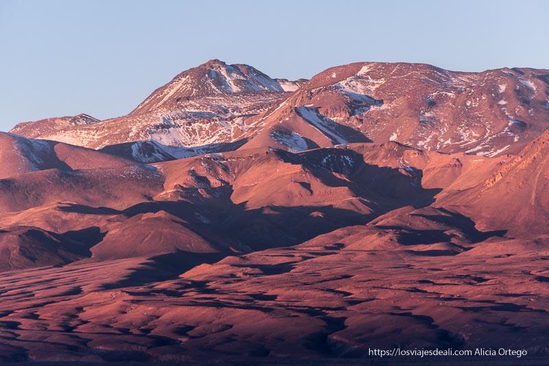 montañas con algo de nieve y desierto rojo por la luz del atardecer San Pedro atacama