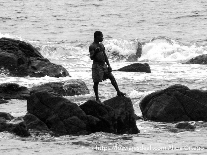 pigmeo baka pescando con un hilo  sobre unas rocas