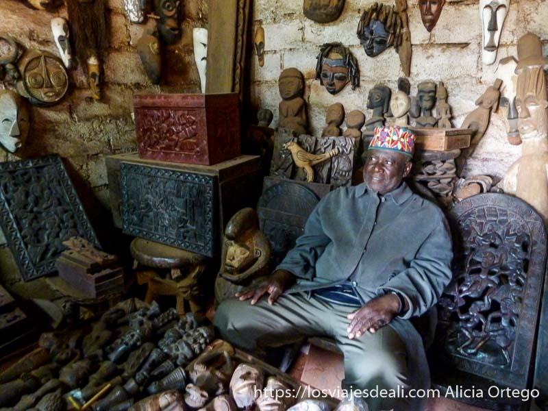 comerciante en su tienda llena de estatuillas de madera, fetiches, cofres... en foumban