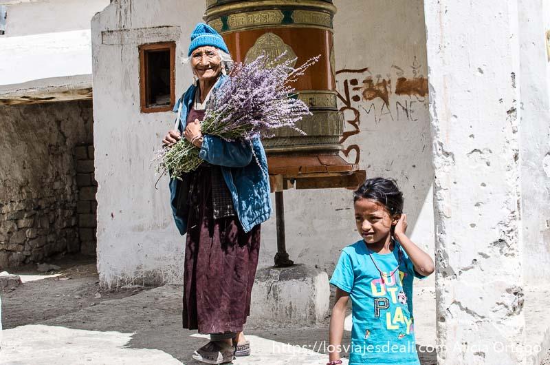 anciana con ramo de flores silvestres junto a campana de oración