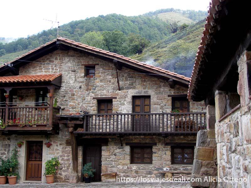 casas de piedra con bonitos balcones y el monte detrás reserva saja nansa
