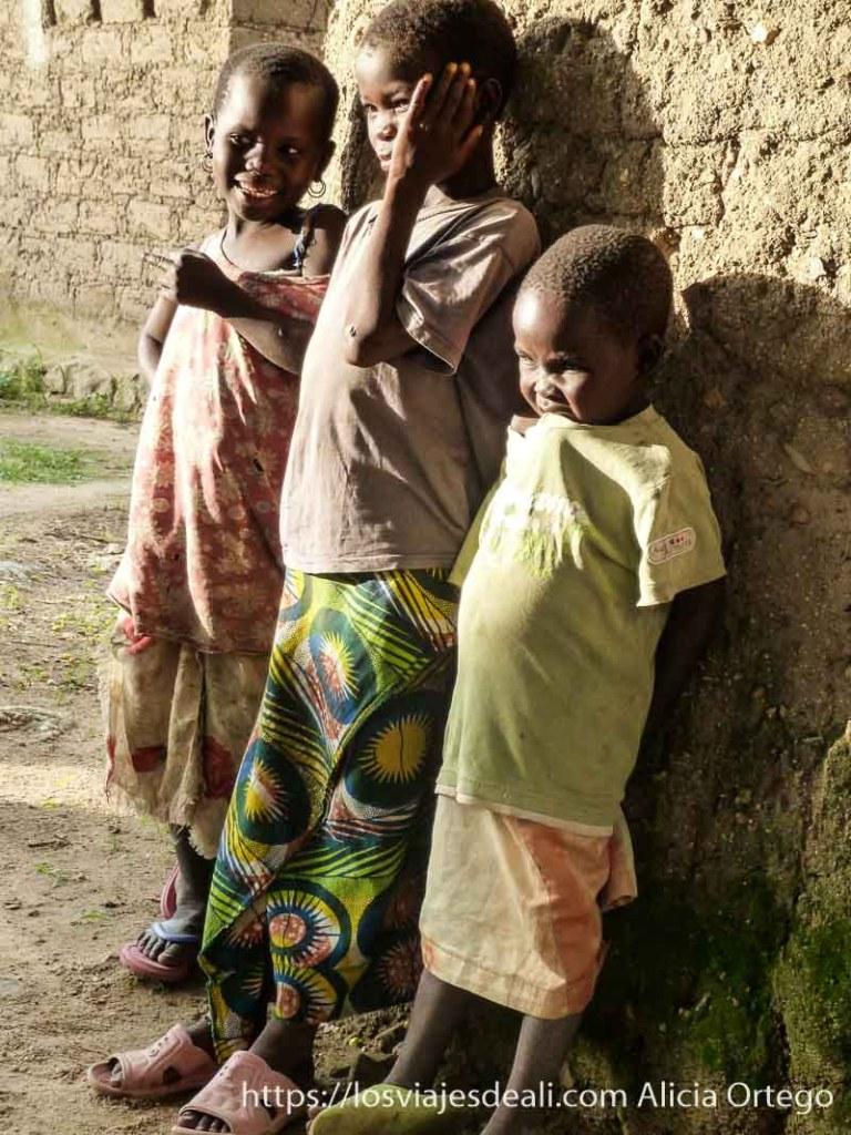 tres niñas apoyadas en pared de adobe con luz de atardecer rumsiki camerún