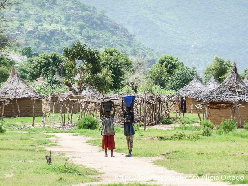 niños con barreños en la cabeza junto a sus casas trekking en el monte ziver