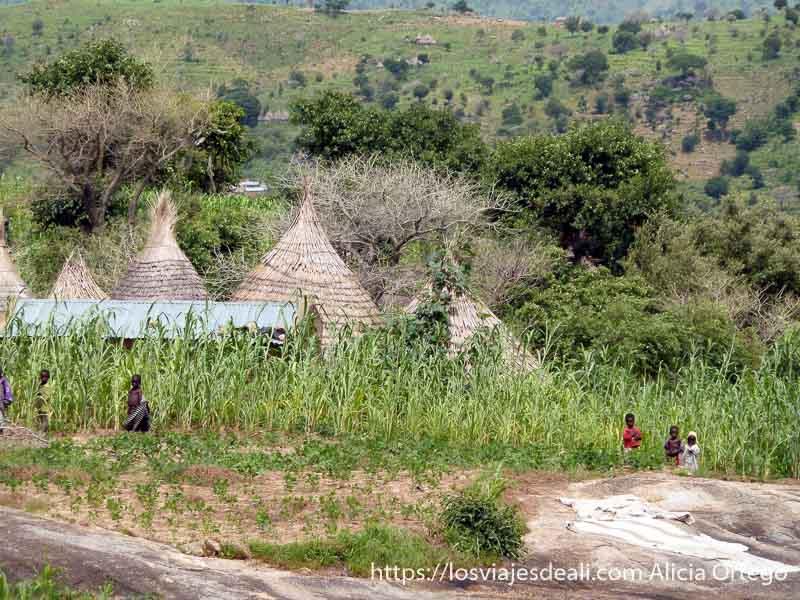 niños pequeños junto a campo de mijo y tejados de paja de sus casas trekking en el monte ziver