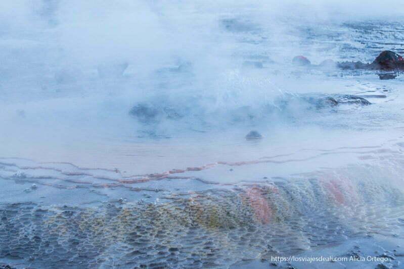 suelo revestido de capas de minerales de distintos colores con vapor de geysers del tatio