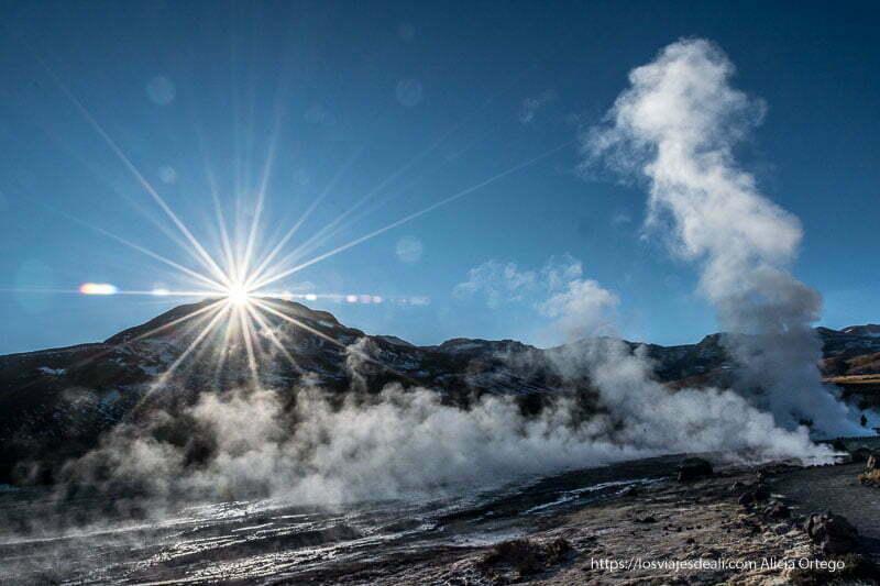 sol saliendo por encima de la montaña y vapores de geysers del tatio