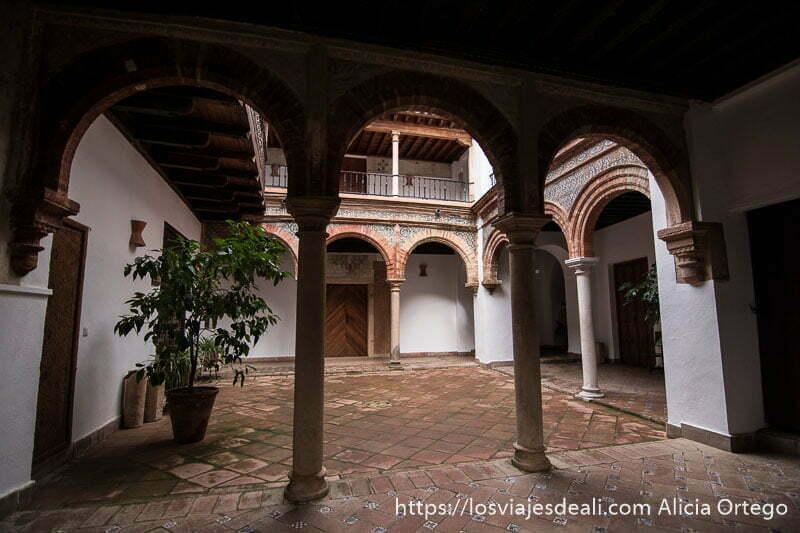 patio interior con arcos decorados con azulejos y ladrillo y suelo de cerámica escapada a ronda