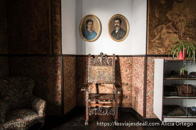 silla antigua con retratos de hombre y mujer en la pared en la casa de don bosco escapada a ronda