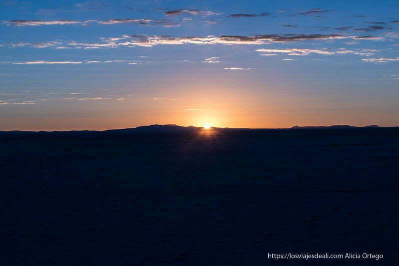 sol saliendo por el horizonte amanecer en el salar de uyuni