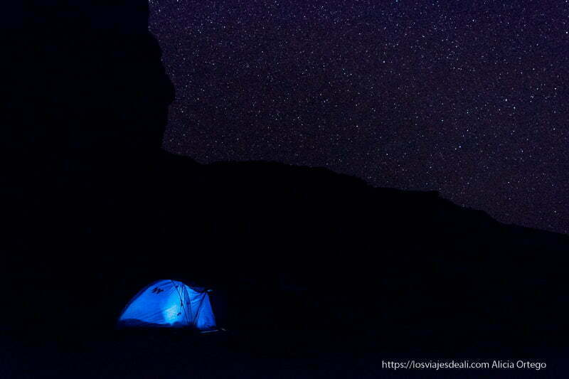 noche estrellada con tienda de campaña de color azul iluminada en la noche