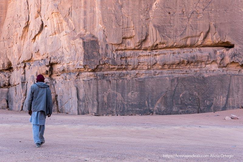 tuareg andando hacia una pared llena de grabados de jirafas y hombres con lanzas en el tassili