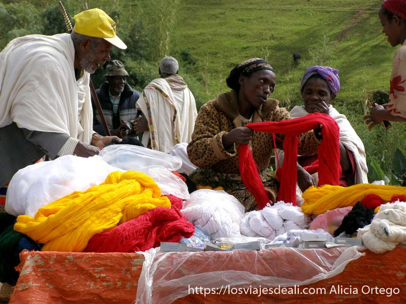 mujer vendiendo madejas de algodón blancas, rojas y amarillas