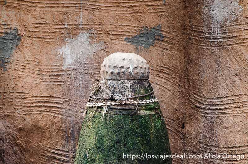 fetiche hecho con figura cilíndrica de barro y olla de cerámica en parte superior boca abajo