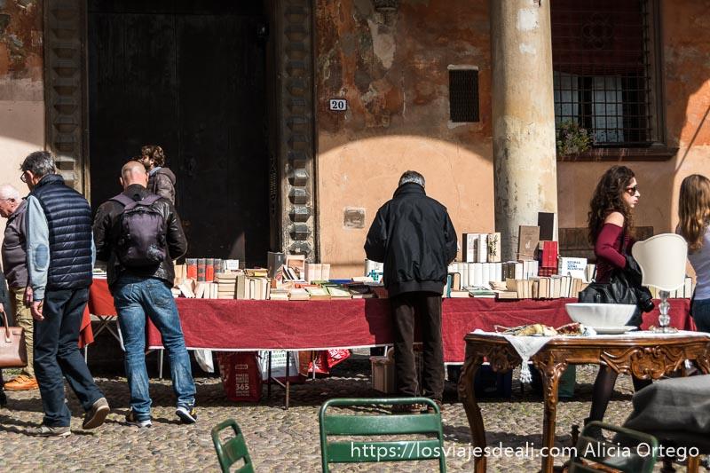 dos hombres mirando en un puesto de libros y al fondo una columna y el portal de un palacio de bolonia