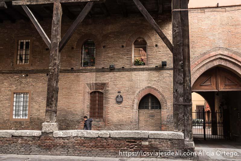 casa medieval de ladrillo con grandes vigas de madera oscura soportando piso superior